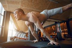 El entrenamiento del hombre del pectoral de la posición del pino en el pus del gimnasio sube Fotografía de archivo libre de regalías
