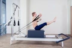 El entrenamiento del reformador de Pilates ejercita al hombre en el gimnasio Imágenes de archivo libres de regalías
