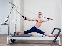 El entrenamiento del reformador de Pilates ejercita al hombre en el gimnasio Imagenes de archivo