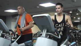 El entrenamiento divertido gordo del hombre en un elipsoide que sostiene la hamburguesa, cerca de él deportista hermoso joven est