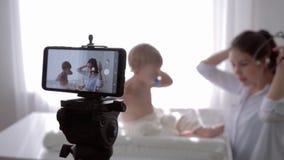 El entrenamiento en línea, hembra del médico de cabecera con el estetoscopio escucha el latido del corazón y la respiración del n almacen de metraje de vídeo