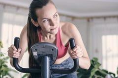 El entrenamiento europeo de la mujer cardiio se resuelve en casa en la bicicleta estática Concepto para la pérdida de peso Chica  fotografía de archivo libre de regalías