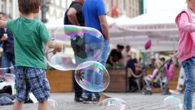 El entretenimiento de los niños, los niños felices juega con las burbujas de jabón en área de la ciudad en fin de semana almacen de metraje de vídeo