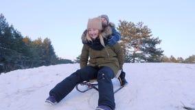 El entretenimiento del invierno, la madre feliz y el hijo montan en trineo en nieve en el bosque en el aire abierto metrajes
