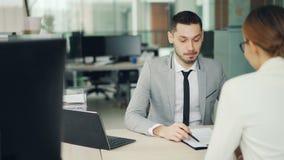 El entrevistador alegre del hombre está hablando con la candidata para la oferta de empleo que se sienta en el escritorio en ofic metrajes