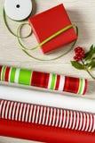 El envoltorio para regalos rojo, blanco y verde de la Navidad suministra los rollos del papel, de la caja de regalo, de cintas y  Imagen de archivo libre de regalías