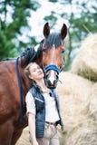 El equestrian bonito joven del adolescente abraza su caballo preferido Imagen de archivo