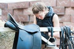El equestrian del adolescente limpia la silla de montar de cuero negra del caballo Foto de archivo