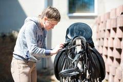 El equestrian del adolescente limpia la silla de montar de cuero negra del caballo Imagenes de archivo