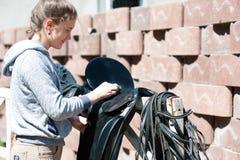 El equestrian del adolescente limpia la silla de montar de cuero negra del caballo Fotos de archivo libres de regalías