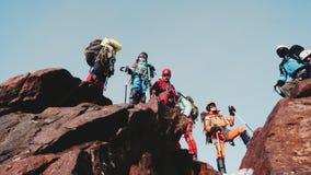 El equipo amistoso de escaladores que se colocan encima de una montaña y felizmente celebra su subida encima de la colina escarpa metrajes