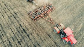 El equipo arable cultiva la tierra en un campo extenso, visión superior metrajes