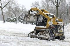 El equipo con la paleta limpia la nieve en la calle, New York City Imagenes de archivo