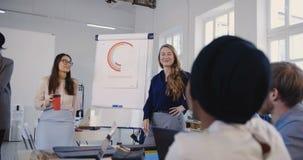 El equipo corporativo multiétnico está escuchando la mujer de negocios rubia sonriente que da seminario de las ventas en la reuni almacen de video