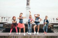 El equipo creativo de muchachas adolescentes atractivas está presentando al aire libre en el parque cerca de las fuentes Foto de archivo libre de regalías