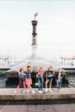 El equipo creativo de muchachas adolescentes atractivas está presentando al aire libre en el parque cerca de las fuentes Imagen de archivo