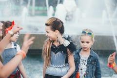 El equipo creativo de muchachas adolescentes atractivas está presentando al aire libre en el parque cerca de las fuentes Imagen de archivo libre de regalías