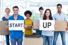 El equipo creativo del negocio que sostiene la cartulina escrita empieza para arriba Imagen de archivo