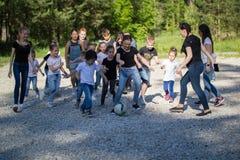 El equipo de adolescentes que juegan a fútbol de la yarda con los niños combina en el día soleado Imagen de archivo libre de regalías