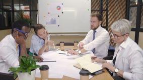 El equipo de arquitectos multi de la raza que trabajan en casa blueprints junto en oficina almacen de video