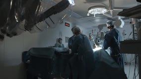 El equipo de cirujanos prepara al paciente a la cirugía robótica como mínimo invasor almacen de video