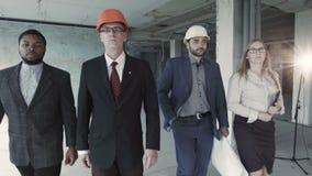 El equipo de constructores en trajes, casco, movimiento, mira directamente en cámara Hombre negro, ingeniero envejecido almacen de video