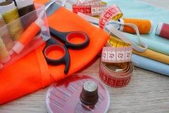 El equipo de costura incluye los hilos de diversos colores, del dedal y de otros accesorios de costura en la tabla de madera herr Fotos de archivo