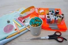 El equipo de costura incluye los hilos de diversos colores, del dedal y de otros accesorios de costura en la tabla de madera herr Fotografía de archivo