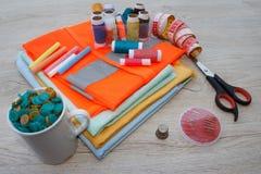 El equipo de costura incluye los hilos de diversos colores, del dedal y de otros accesorios de costura en la tabla de madera herr Imagen de archivo libre de regalías