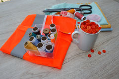 El equipo de costura incluye los hilos de diversos colores, del dedal y de otros accesorios de costura en la tabla de madera herr Fotos de archivo libres de regalías