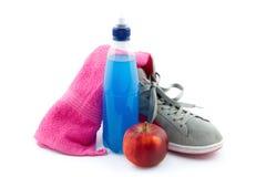 El equipo de deportes tal como zapatillas de deporte, energía bebió, toalla y manzana Imágenes de archivo libres de regalías