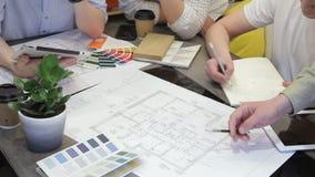 El equipo de diseñadores trabaja sentarse en la tabla en oficina usando la tableta almacen de video