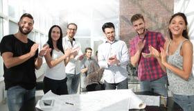 El equipo de diseño dio una ovación de pie en la oficina creativa foto de archivo
