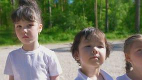El equipo de diversas edades de los pequeños niños caucásicos se alineó en línea adentro en el día soleado al aire libre metrajes