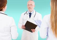 El equipo de doctores que discutían algo aisló en el fondo azul, falso para arriba fotografía de archivo