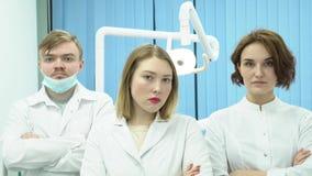 El equipo de doctores se coloca con sus manos cruzadas media Tres doctores en los uniformes blancos se colocan con sus brazos cru metrajes