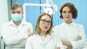 El equipo de doctores se coloca con sus manos cruzadas media Tres doctores en los uniformes blancos se colocan con sus brazos cru almacen de video