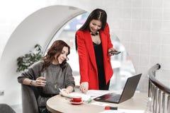 El equipo de dos mujeres jovenes elegantes de los interioristas est? trabajando en la oficina en el proyecto de dise?o imagenes de archivo