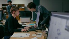 El equipo de Emploees está discutiendo el funcionamiento de proyecto en la oficina con los ordenadores metrajes