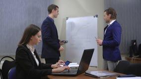 El equipo de empresarios jovenes Trabajan así como los documentos y las figuras En la oficina almacen de metraje de vídeo
