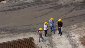 El equipo de encargados en cascos amarillos está hablando en emplazamiento de la obra