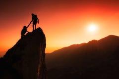 El equipo de escaladores ayuda a conquistar la cumbre Fotos de archivo libres de regalías