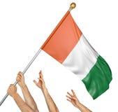 El equipo de gente da el aumento de la Costa de Marfil bandera nacional Imagenes de archivo
