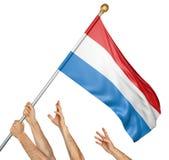 El equipo de gente da el aumento del Luxemburgo bandera nacional Imagen de archivo