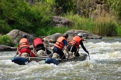 El equipo de gente en un catamarán inflable rema encima de la corriente en umbrales Fotografía de archivo