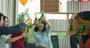 El equipo de gente joven celebra con la tostada y tintinear aumentando los vidrios en su oficina almacen de video