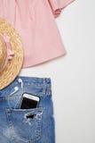 El equipo de la blusa, dril de algodón pone en cortocircuito, sombrero de paja en el fondo blanco Imagenes de archivo