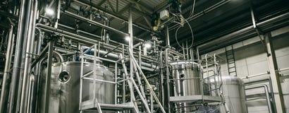 El equipo de la cervecería, las tuberías de acero inoxidables industriales conectó con los tanques o las cubas para la producción fotografía de archivo