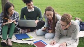 El equipo de la cooperación es que se sienta y que estudia cerca de campus universitario metrajes