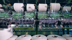 El equipo de la fábrica arrolla los hilos sobre los ovillos grandes automáticamente almacen de video